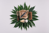 top view of arranged barber tools for shaving on green leaves isolated on grey - 191496033