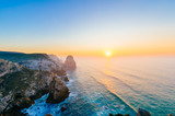 Amazing stunning unbelievable sunset at atlantic ocean in Portugal. Cape Rock fantasy seascape. View from big height at colorful scenic sea with rocks and mountains in evening. Tropical paradise.