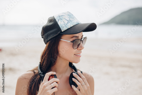 attractive woman in cap and sunglasses with headphones at beach