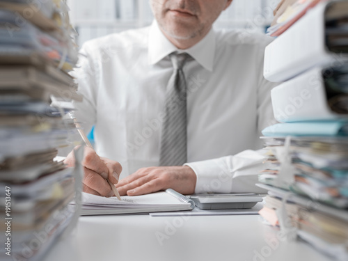 Corporate executive in the office, he is overloaded with work and writing a financial report