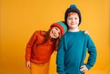 Two happy little children wearing warm hats. - 191515640