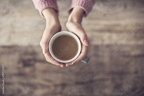 Woman holding coffee cup wooden background