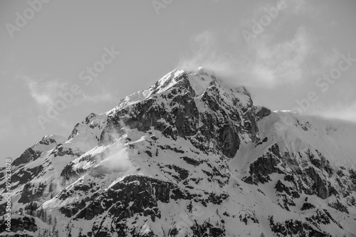 Snow covered mountain peak standing tall in the gusts of wind - 191523878