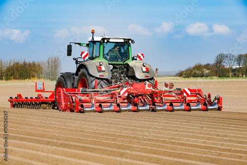 Fotobehang Trekker Traktor mit Front-Roller und Dammfräse beim Kartoffelanbau - 1071