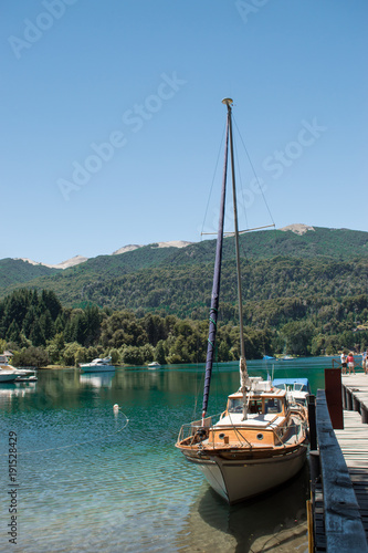 Fotobehang Zeilen Sailboat moored to the dock on a blue lake with mountains in the background