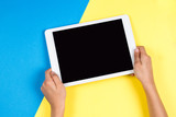 Fototapety Kid hands with tablet computer on blue and yellow background