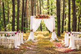 Beautiful elegant wedding decorations of place for ceremony outside in old wood with huge pines trees. Horizontal color photography. - 191538039