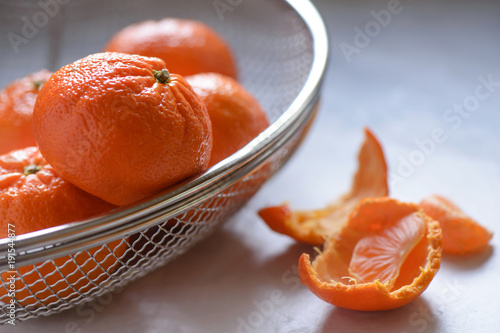 Mandarin oranges in a wire basket with pieces of peel and a segment