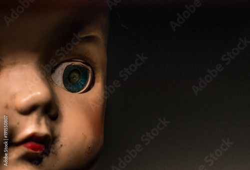 Half face portrait of old doll with dirty face.