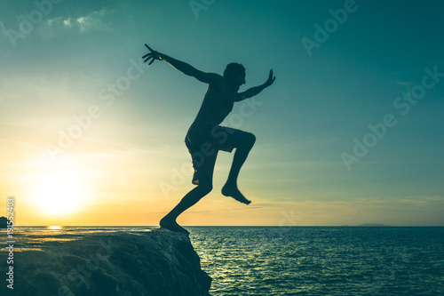 Man jumping over a cliff into the sea on sunset in Koh Phangan island, Thailand. Vintage effect. Dare, fearless concept. Two out of three series