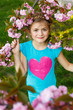 Beautiful little girl in blossom cherry garden on beautiful spring day