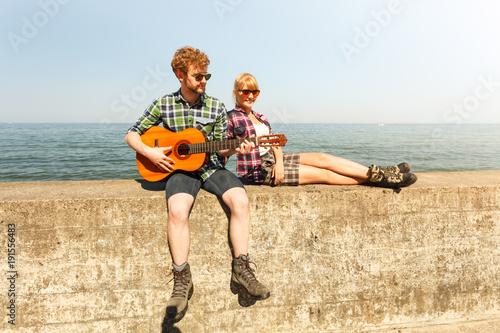Fotobehang Muziek Young man hipster playing guitar for woman.