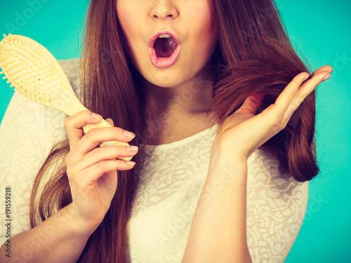 Foto Murales Shocked amazed woman holding hair brush