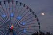 A full moon rises behind a Ferris wheel in Dallas.