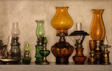 Collection of old-styled kerosene lamps on shelf
