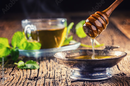 Honey. Honey and honey dipper on rustic oak table. Hot herb tea in the background