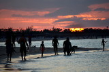Dramatic sunset over a tropical beach in the Caribbean (Cayo Coco, Cuba). Silhouettes of people walking on the shore.  - 191585213