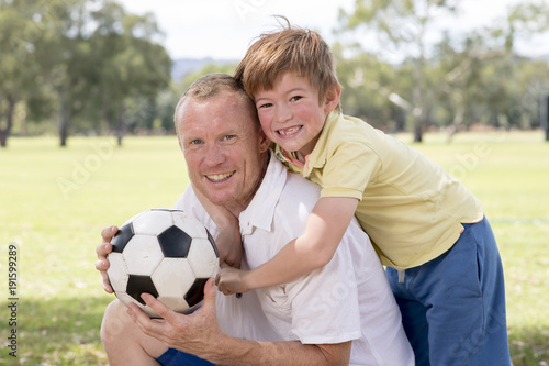 young happy father and excited 7 or 8 years old son playing together soccer football on city park garden posing sweet and loving holding the ball