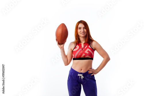 Fotobehang Voetbal young red-haired woman in sportswear smiling and posing with rugby ball on white isolated background