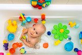 Baby boy taking a bath, playing with colorful toys - 191605201