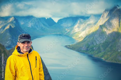 Fotobehang Blauwe jeans Portrait of a tourist man, standing on a peak of a mount Reinebringen and looking in camera. Beautiful mountain landscape in the background. Nature of Norway, Lofoten Islands