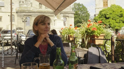 Woman sitting in an open air caffee looking to side watching around