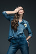 beautiful girl closing eye and posing in denim shirt, isolated on grey