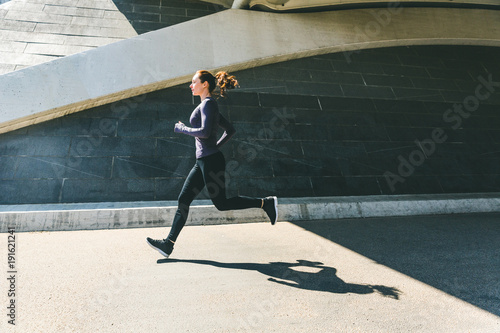 Fotobehang Hardlopen Woman jogging or running, side view with shadow