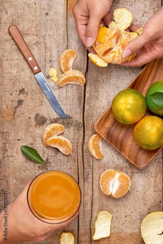 Citrus juice in glass and fresh mandarin orange on wooden background