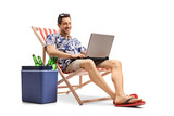 Tourist with a laptop sitting in a deck chair next to a cooling box - 191629055
