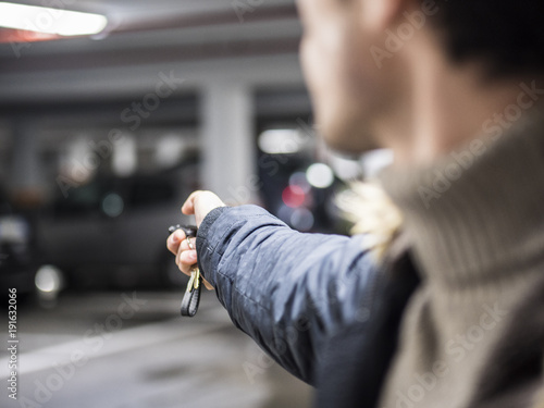 Young trendy man in outerwear standing on parking using alarm remote control.