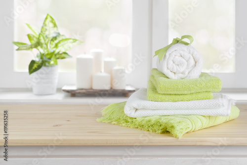 Leinwanddruck Bild Spa towels on wooden table over blurred salon window background