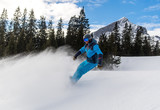 Junger Snowboardfahrer fährt die Piste hinunter