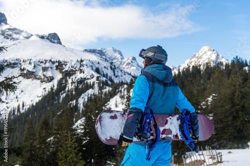 mata magnetyczna Junger Snowboarder steht am Rande der Piste und blickt auf die Berge