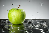 Green apple with water drops on grey background