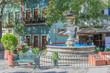 Fountain surrounded by a green iron fence, a green iron bench, some greenery, umbrellas for dining, and colorful two-story buildings, in the San Fernando Plaza, in Guanajuato, Mexico