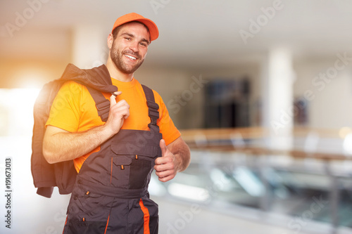 Portrait of smiling mechanic. Man in uniform with thumb up.