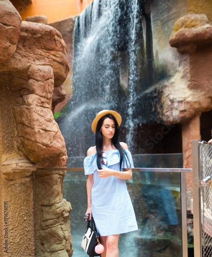 Woman posing near waterfall