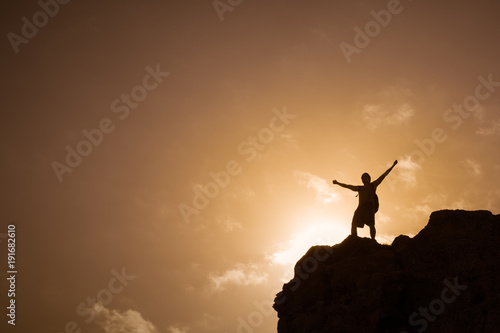Man standing on top a mountain feeling free.