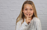 Portrait of happy smiling 10 years old kid girl showing silence gesture - 191685623