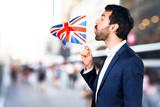 Handsome man holding an UK flag on unfocused background - 191685806