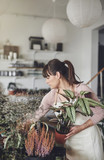 Young female florist busy working in her flower shop - 191695455