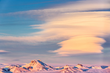 Icelandic landscape with snow-capped mountain peaks and spectacular cloud formations, near Gullfoss, at sunset.