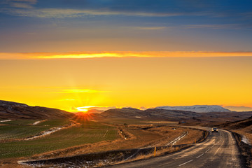Winding road with lonely car crosses farm fields and mountains in rural Iceland at sunset.