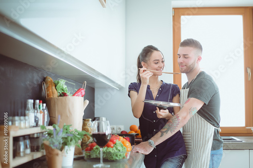 Couple cooking together in their kitchen at home