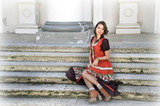 young beautiful brunette in boho style costume sits on the steps of the Palace - 191701402