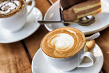Cup of hot Cappuccino coffee on wooden table at cafe - 191715607