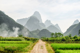 Amazing dirt road through green rice fields and karst mountains - 191715627