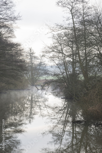 Keuken foto achterwand Wit Low hanging misty morning landscape over calm stream in English countryside landscape image