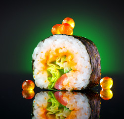Sushi roll over black background. Sushi roll with tuna, vegetables, flying fish roe and caviar closeup. Japanese food